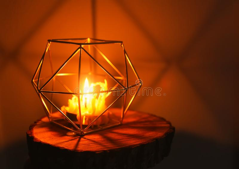 Hand made bee wax candle in a candleholder on wooden slice. Warm light of hand made natural bee wax dying candle in a candleholder on wooden slice royalty free stock images