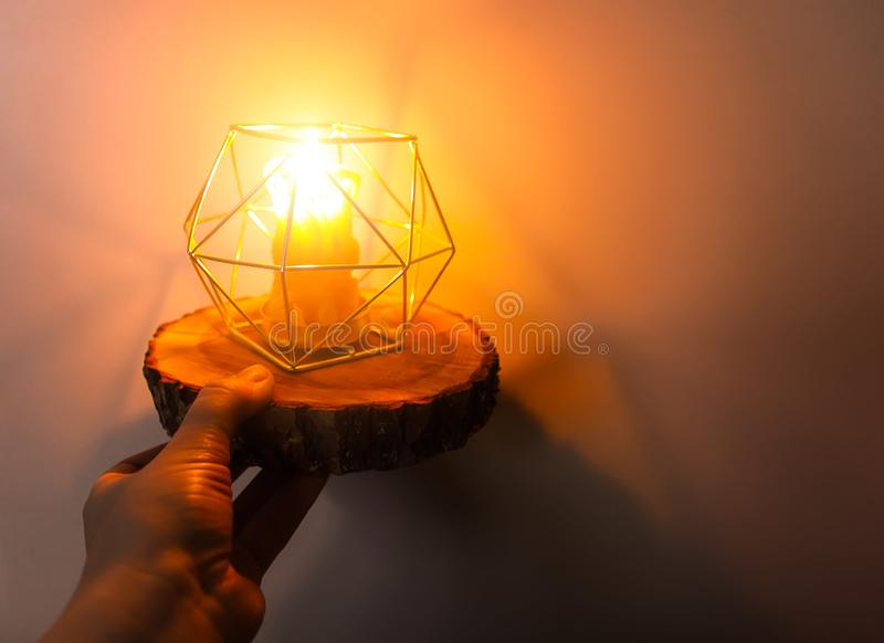 Hand made bee wax candle in a candleholder on wooden slice. Warm light of hand made natural bee wax dying candle in a candleholder on wooden slice stock photography