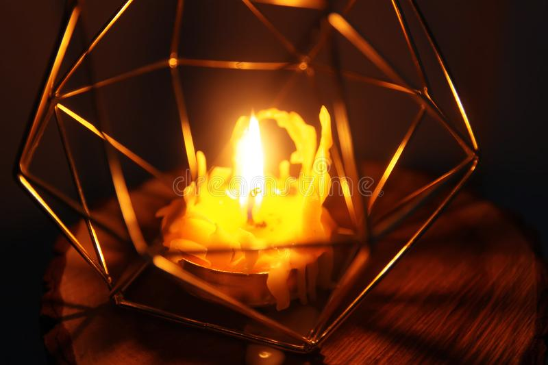 Hand made bee wax candle in a candleholder on wooden slice. Warm light of hand made natural bee wax dying candle in a candleholder on wooden slice stock image