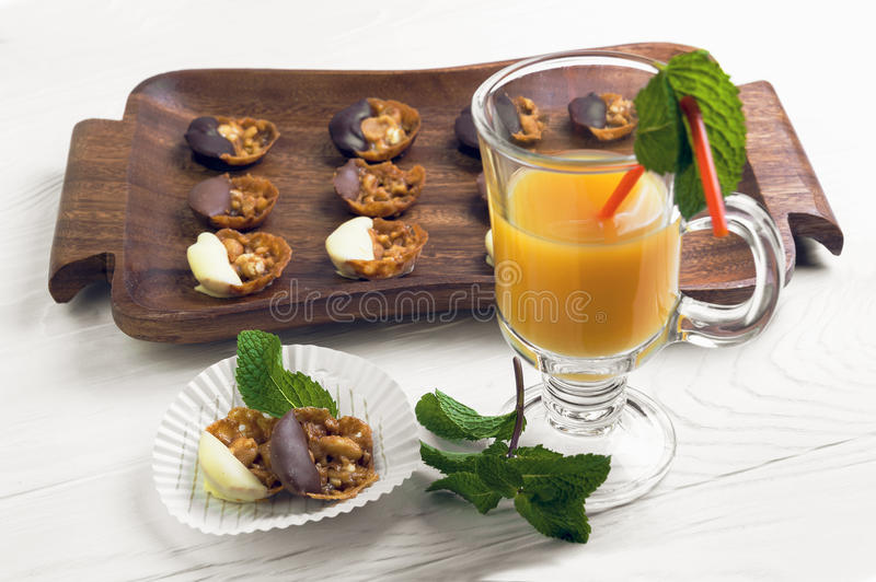 Hand-made chocolates. On a white wooden table tray with hand-made chocolates, a glass of orange juice, mint sprigs royalty free stock photos