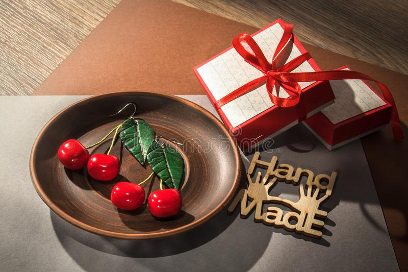 Hand made custom cherry polymer clay earrings on wooden plate royalty free stock image