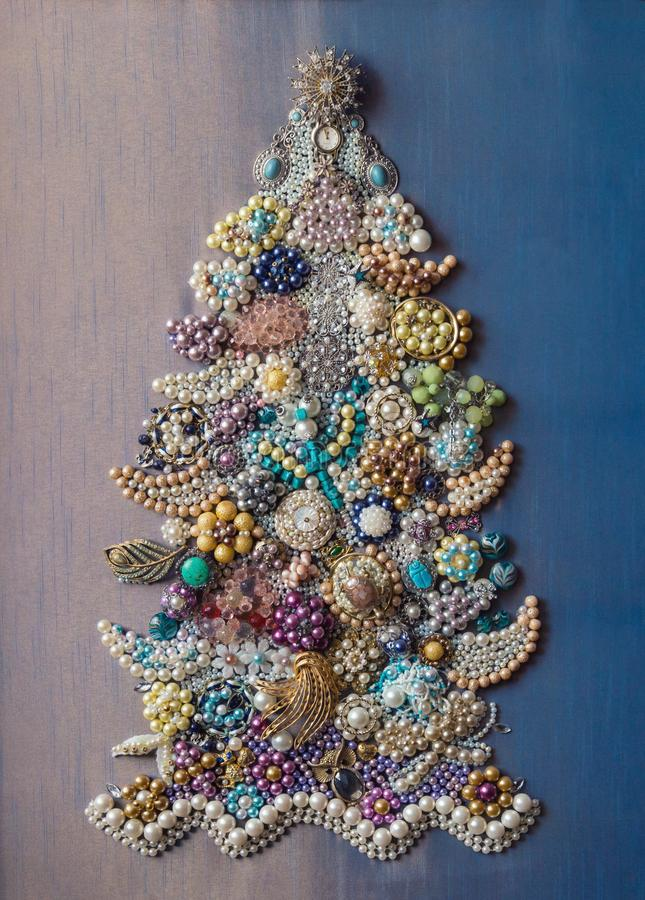 Hand-made. Decorative Christmas tree made of jewelry on a blue gradient background. Decorative Christmas tree made of jewelry on a blue gradient background royalty free stock photography