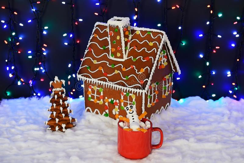 The hand-made eatable gingerbread house, marshmallow little men in mags,  New Year tree, snow decoration stock image