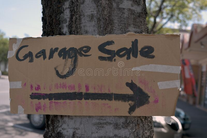 Hand made garage sale sign taped to tree stock photos