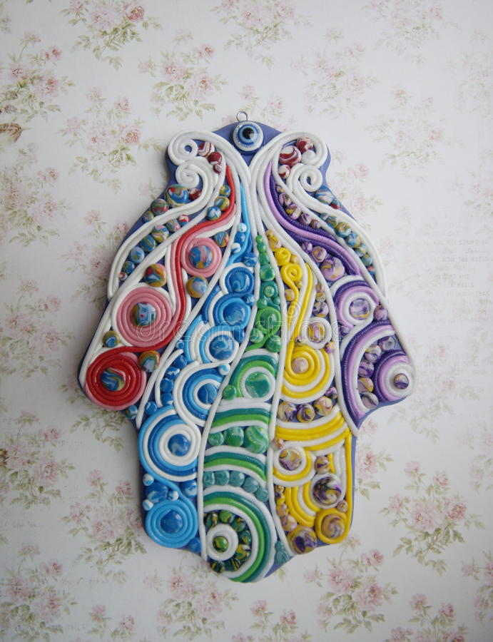 The hand made hamsa. Hand-molding khamsa from polymer clay on a wooden base royalty free illustration