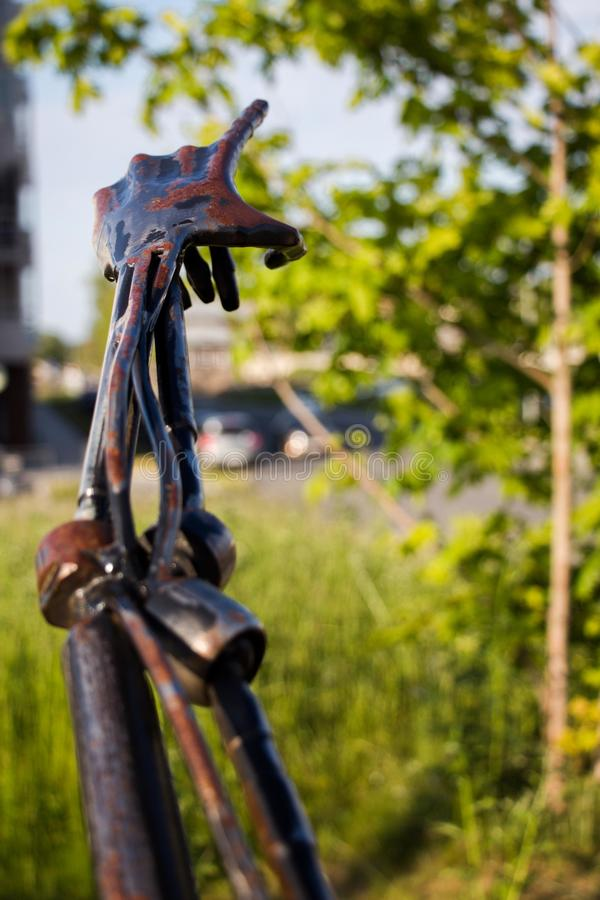 A hand made of iron points to the sky and to a green tree. The hand is slightly covered in rust. stock photography