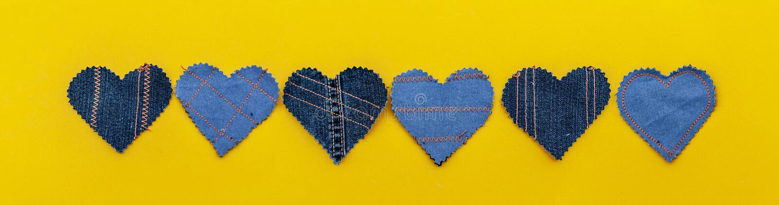 Hand made Jeans hearts on a yellow background. Flat lay, top view, minimal style, copy space for text. Symbol of love. For Valentine`s day greeting card or royalty free stock photo