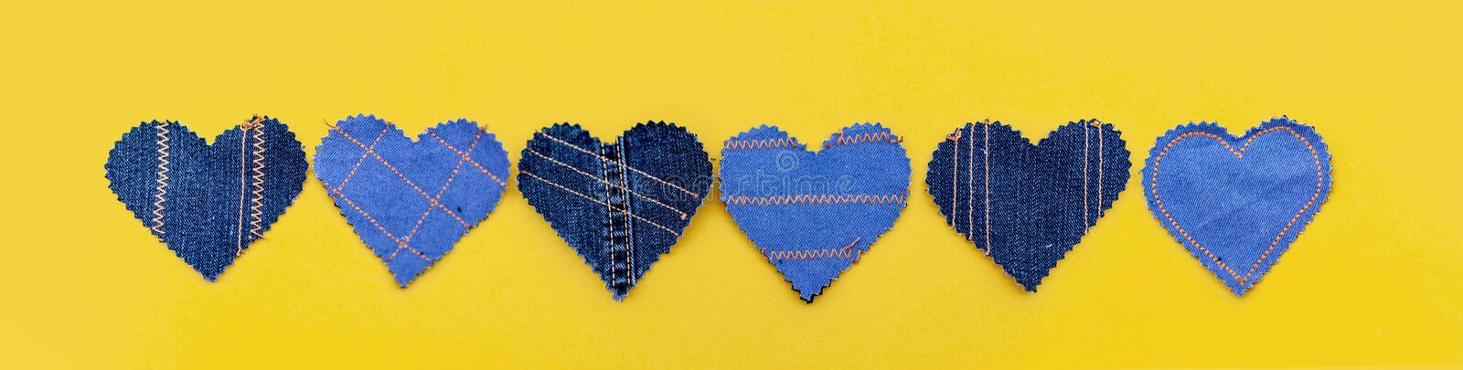 Hand made Jeans hearts on a yellow background. Flat lay, top view, minimal style, copy space for text. Symbol of love. For Valentine`s day greeting card or stock photos