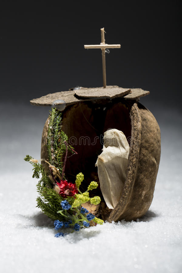 Hand made manger with snow, cross Catholic symbols. On the dark background royalty free stock photo