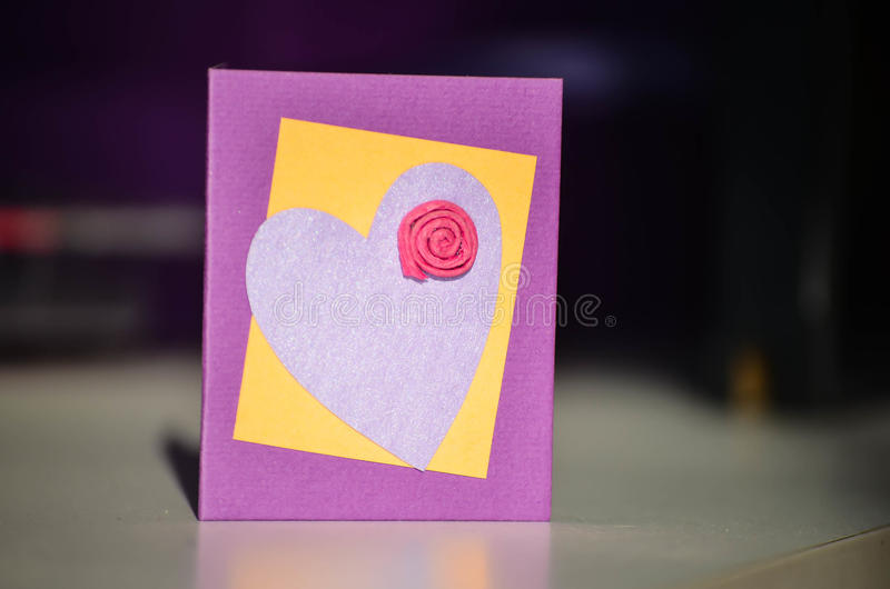 Hand made present card with heart and flower. Hand made purple present card with violet heart and red flower stock photo