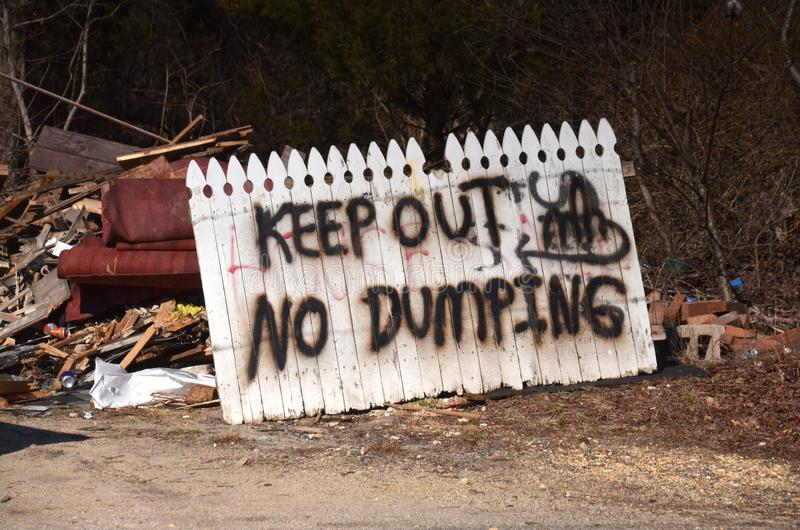 Keep Out. A hand made sign from a piece of broken fence warning Keep Out No Dumping stock photography
