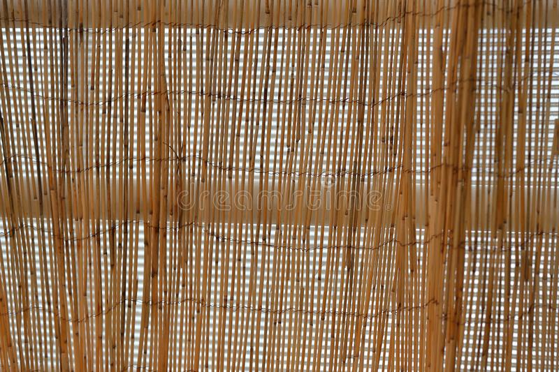 Hand made thin bamboo blinds. Craft blinds made of thin brown bamboo in the doorway stock photos