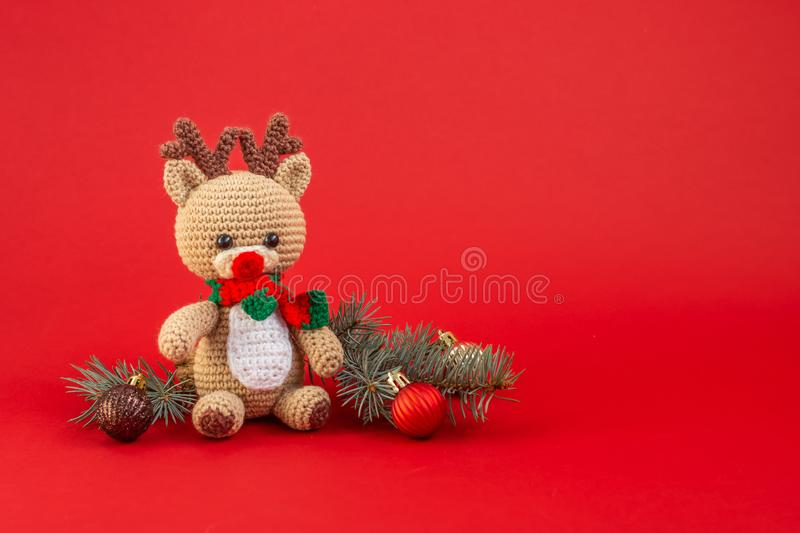 Hand-made christmas deer, spruce twigs and christmas balls on red background royalty free stock photography