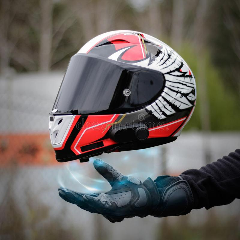 Hand magically holds a motorcycle sports helmet. Close up. Hand in a leather glove stock photo