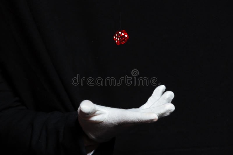 Hand of magician in white glove showing tricks with dice royalty free stock photo