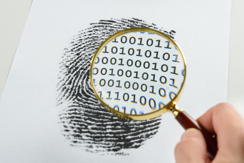 Hand with magnifying glass over a finger print stock photography