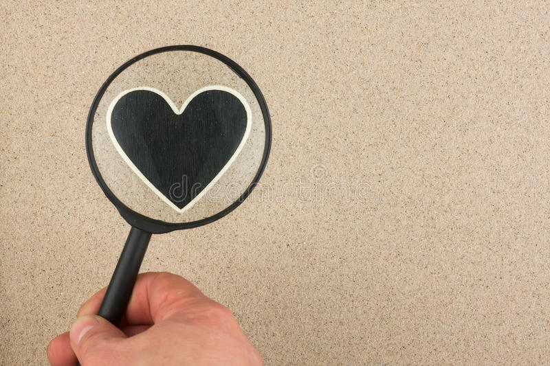 Download Hand With Magnifying Glass Over The Heart In The Sand Stock Image - Image: 40121925
