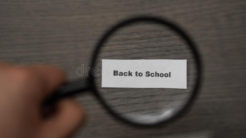 Hand with a magnifying glass on a wooden background. Magnifier enlarges the phrase back to school. Concept of the school stock photo