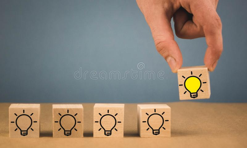 the hand makes a choice and chooses a burning light bulb, a symbol of a fresh idea royalty free stock photo