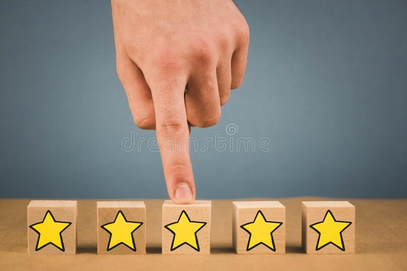 hand makes a choice and chooses one of the stars, on a blue background stock photography