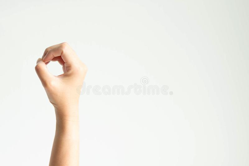 A hand making circle shape; or showing number zero by using thumb touching other fingers on white background. With copy space; concept of decrease in goods stock image