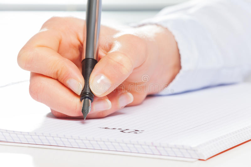 Hand making notes with metallic fountain pen. Close-up picture of woman`s hand making notes on the ring-bound notebook with metallic fountain pen at the table stock photo