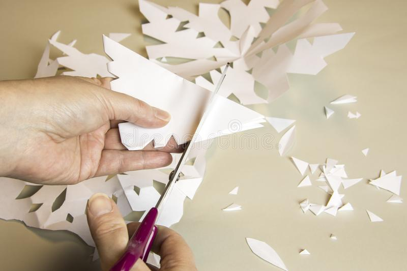 Hand making paper snowflake cutouts. Hand holding handmade paper cutout snowflakes arts and crafts project with scissors stock image