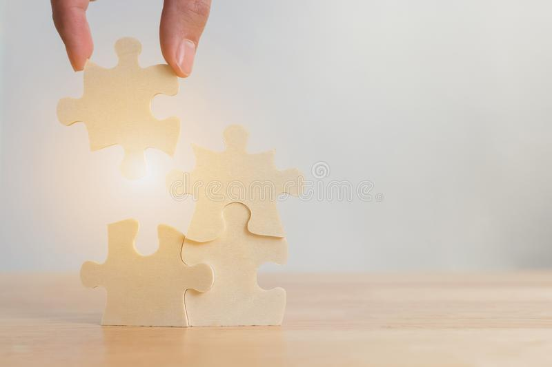 Hand of male or female putting jigsaw puzzle connecting on wooden desk, Strategic management royalty free stock photos