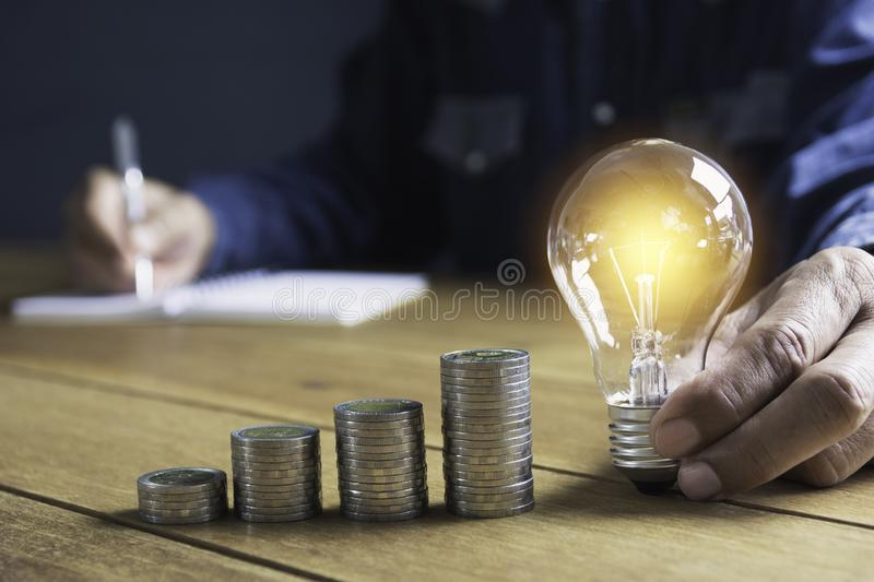 Hand of male holding a light bulb with stack of coins and copy space for accounting, ideas and creative concept stock image