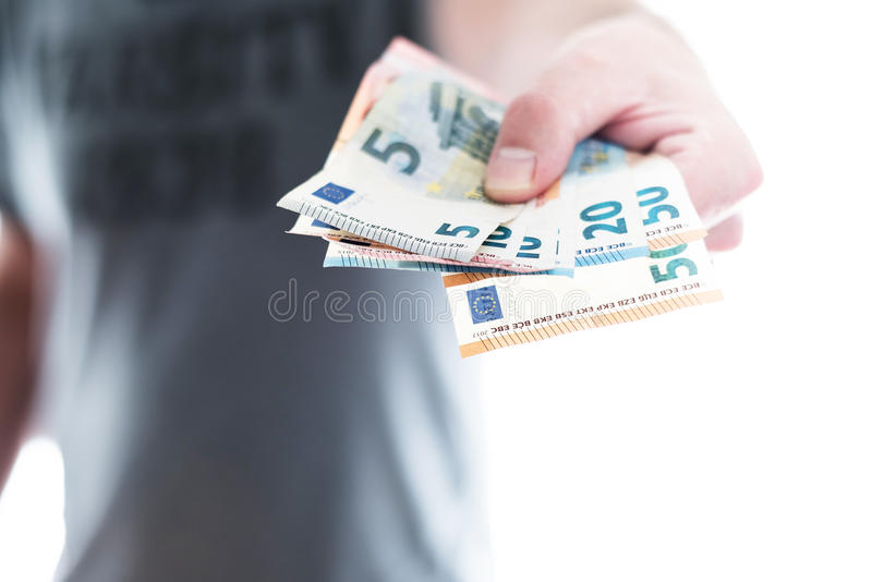 Hand of male person handing over euro banknotes. Hand of male person handing over a couple of different euro bills royalty free stock image