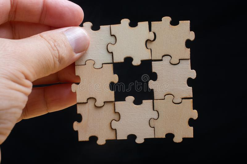 Hand of male trying to connect pieces of jigsaw puzzle. Man holding last piece of jigsaw puzzle as business strategy concept royalty free stock photography