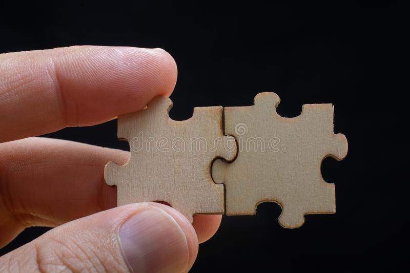 Hand of male trying to connect pieces of jigsaw puzzle. Man holding last piece of jigsaw puzzle as business strategy concept stock photography