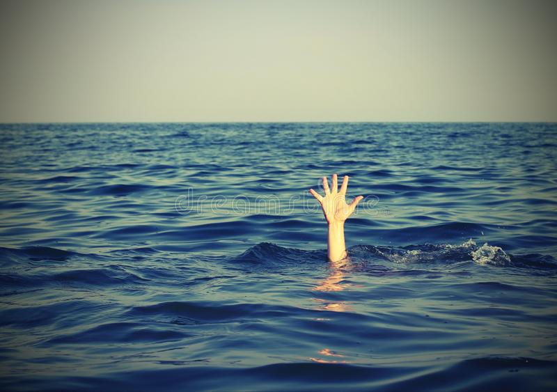 man while asking for help drowning in the sea with vintage effec stock photography