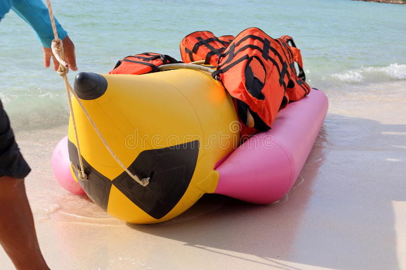 Hand of man with banana boat and safety life jacket on the beach.  stock photo