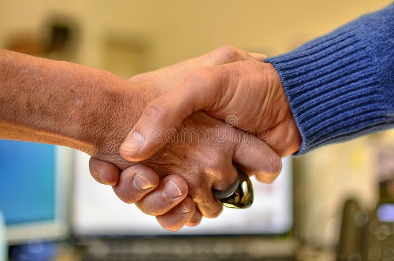 Hand of a man and a Caucasian woman shaking. Against a background of a blurred and indistinguishable office, a hand of a man and a Caucasian woman shaking in royalty free stock photo