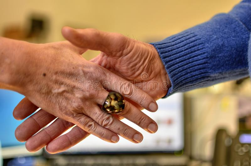 Hand of a man and a Caucasian woman shaking. Against a background of a blurred and indistinguishable office, a hand of a man and a Caucasian woman shaking in stock image