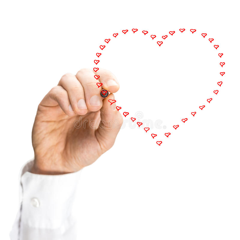 Hand of a man drawing on a screen a heart shape. Hand of a man drawing on a virtual screen a heart shape made of small hearts, concept of unity, love and charity royalty free stock images