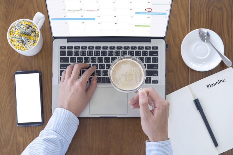 Hand of man drinking milk coffee and using computer laptop  with smartphone for working on desk at coffee shop, Working and royalty free stock photo