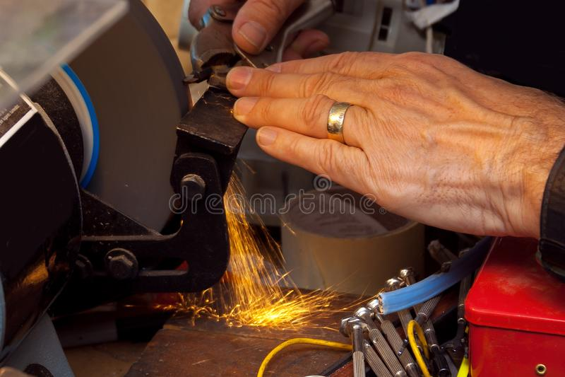 Hand of a Man Grinding a Drill Bit royalty free stock images