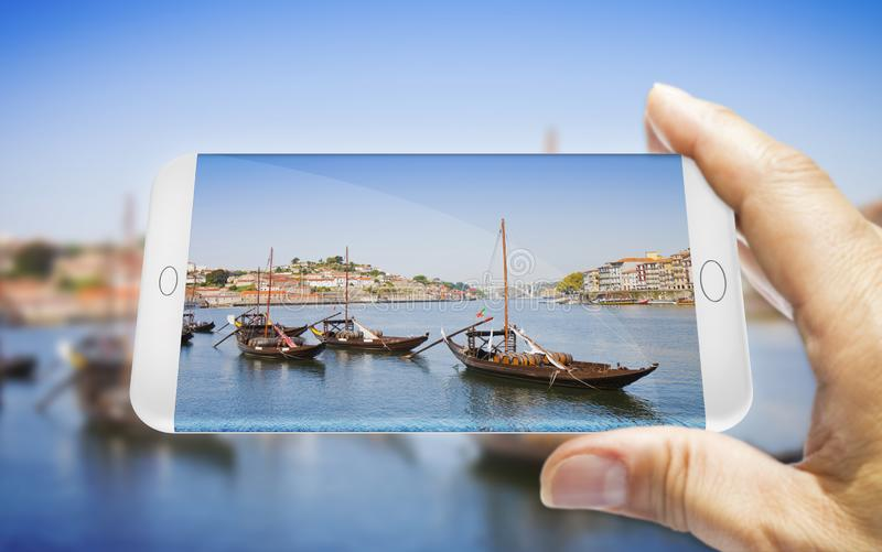 Hand of man holding a smartphone with a picture of a typical portuguese boats used in the past to transport the famous port wine. Portugal - 3D render concept stock photography
