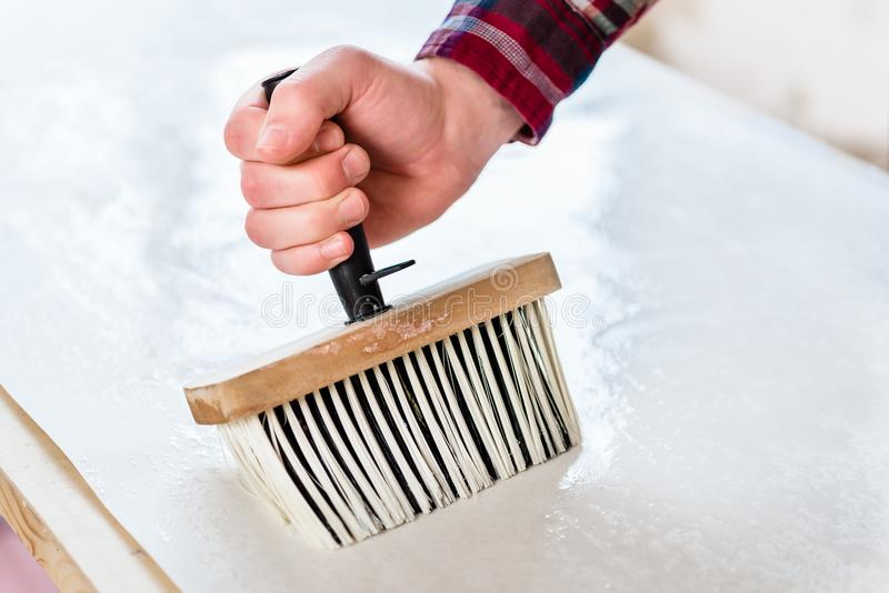 Hand of a man holding a synthetic brush while applying paste stock photos