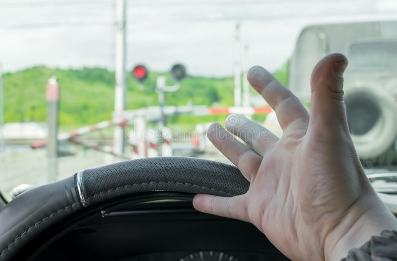 The hand of man inside the car. The car stopped in front of a closed barrier. And a red traffic light before the railway crossing. Man outraged by the situation royalty free stock image