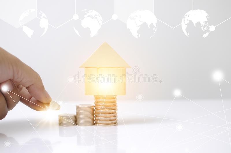 Hand man laying stack coins with wooden blocks house and light effect earth circle map graphic for internet of thing. Saving to bu. Y or loan a home business stock illustration