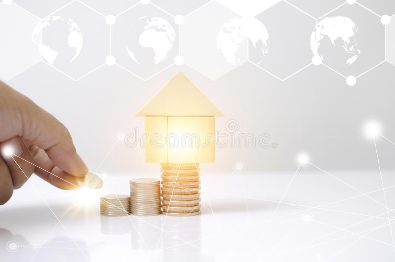Hand man laying stack coins with wooden blocks house and light effect earth circle map graphic for internet of thing. Saving to bu. Y or loan a home business royalty free illustration