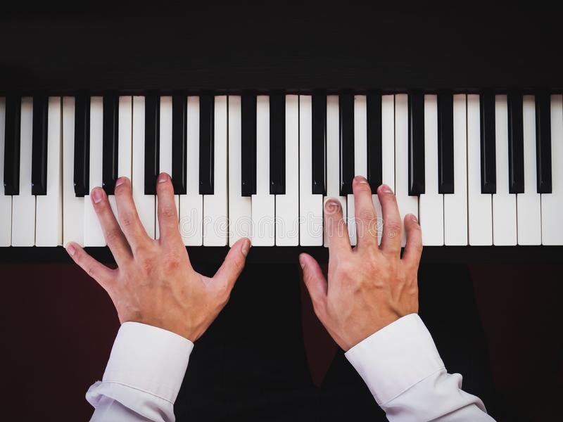 Hand man playing piano. Classical music instrument. Top view stock images