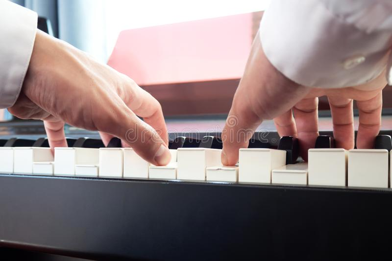 Hand man playing piano. Low angel view.  Classical music instrument royalty free stock photography