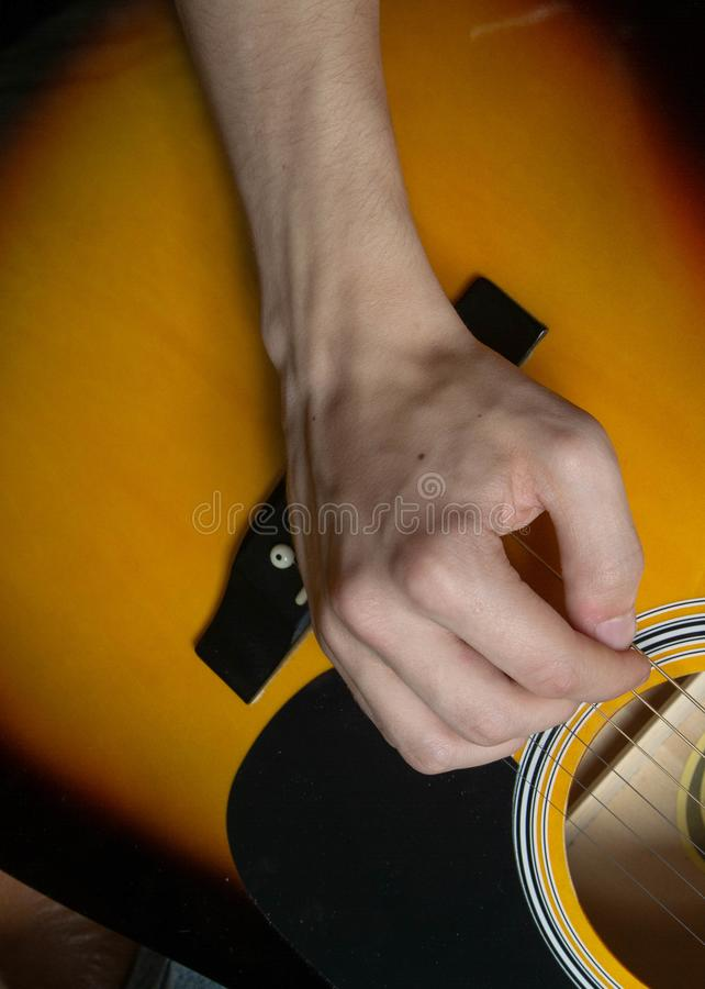 Hand of man playing six-string guitar on wooden background royalty free stock images