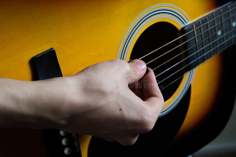 Hand of man playing six-string guitar on wooden background. stock photos