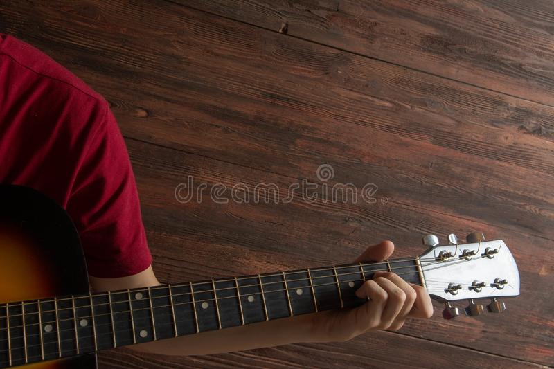 Hand of man playing six-string guitar on wooden background. Template for concert poster stock photo