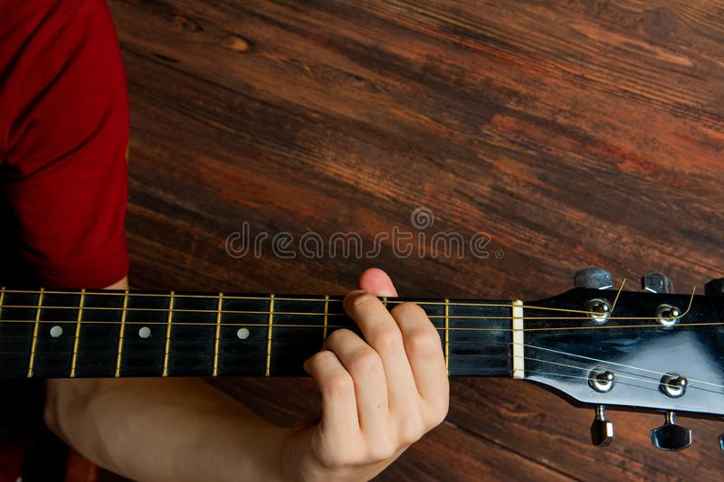 Hand of man playing six-string guitar on wooden background. Template for concert poster royalty free stock image